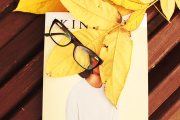 glasses with a magazine on a bench in autumn park