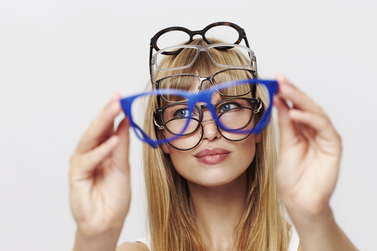 Young blond student choosing spectacles
