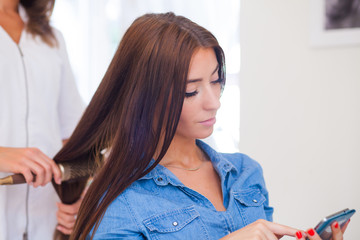 Hairdresser combing hair woman with mobile phone in hairdressing salon.