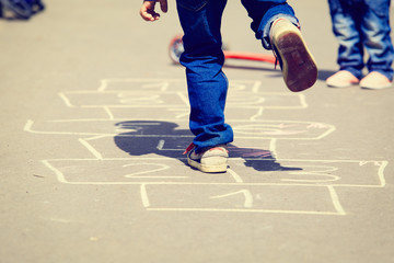 kids playing hopscotch on playground outdoors