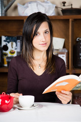 Bella ragazza che beve il tè e legge un libro