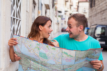 Friends loking on the map on the street. They are on holidays.