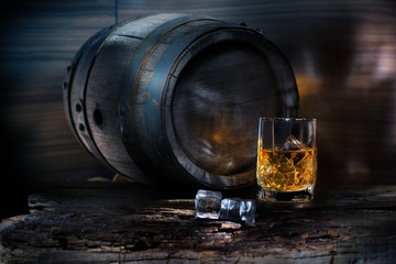 A glass of whiskey with ice on background barrel