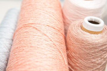 Spools of thread peach color on a white background