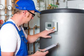 Handwerker kontrolliert im Heizungskeller den Heizungskessel oder Warmwasser Tank
