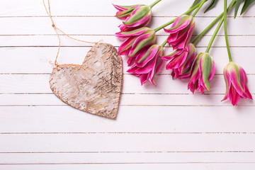 Background with  pink tulips flowers and decorative heart