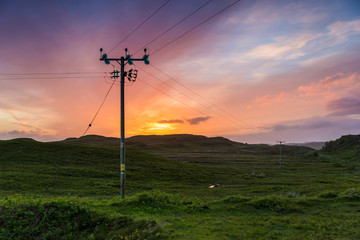 Telephone or electricity line in the fields at sunset