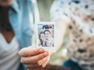 Detail of snapshot taken by a loving couple among the olive trees of a cultivated field in Tuscany during a picnic, Italy, in the background an old blue car. Man holding the instant photo