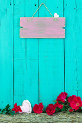 Blank sign with hearts hanging hanging on fence by rose covered log