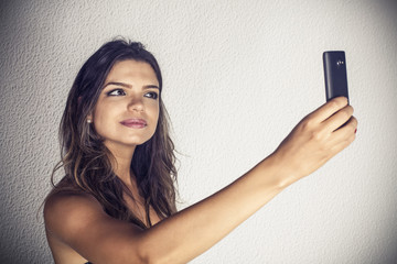 Beautiful girl takes a selfie with mobile phone