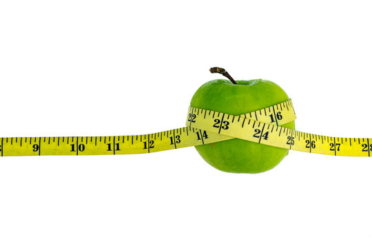 Apple wrapped with measuring tape on white background. Healthy diet concept. Selective focus.