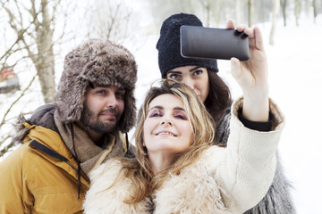 group of person taking selfie in winter forest