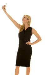 blond woman black business dress side take selfie