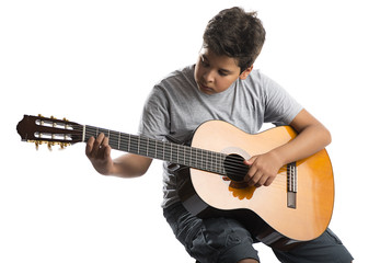 Child on chair playing classical guitar isolated on white background.