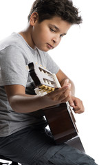 Vertical image of cute little boy playing guitar isolated on white