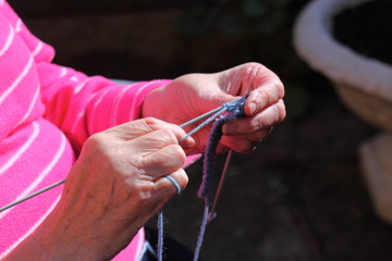 Woman knitting outdoor. Senior lady outdoor in sunshine knitting.