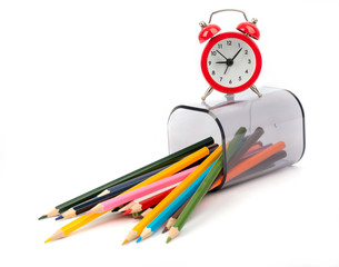 Fallen pencil cup with crayons and alarm clock