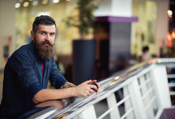 Stylish bearded man with the phone in the hands of a shopping center on the background of shop wsindows