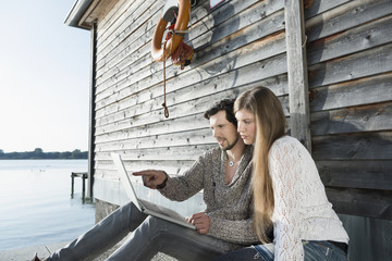 Young couple sitting boathouse using computer