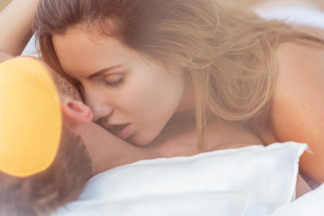 Alluring woman kissing male neck