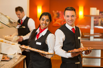 Waitress and waiters posing with food at buffet in a restaurant