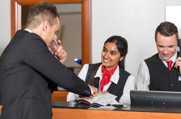 Receptionist at hotel reception assisting guest with city map
