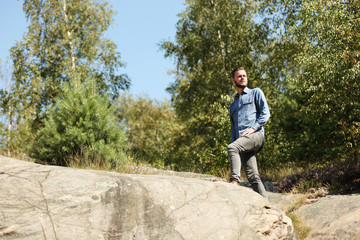 Attractive man wearing a jeans shirt and jeans, standing on top of a mountain looking forward, on a sunny summer day.