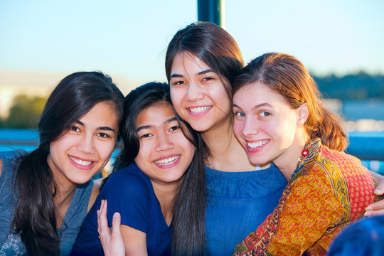 Group of four young women smiling together by lake