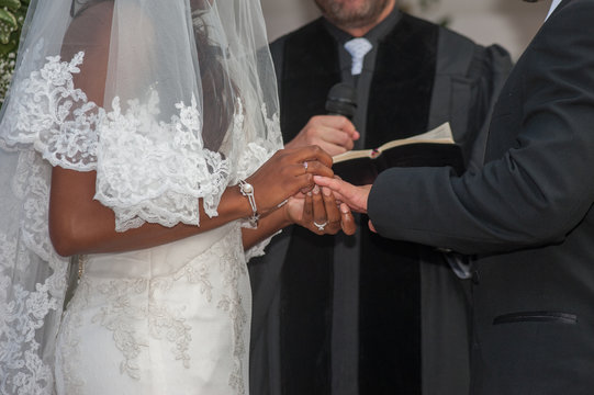 Bride places ring on groom's finger at alter.