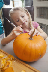 Girl carving pumpkin for Halloween, Bavaria, Germany