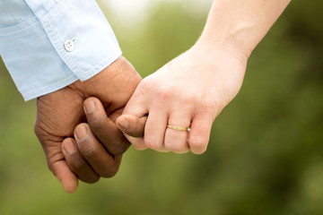 Love.  Rear view of a multiracial couple holding hand.