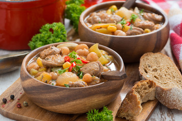 vegetable stew with sausages in a wooden bowl, close-up