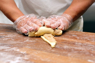 Baker making croissants on the wooden table