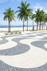 Iconic sidewalk tile pattern with palm trees at Copacabana Beach Rio de Janeiro Brazil