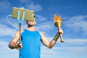 Smiling athlete holding a sport torch taking a selfie using a mobile phone on a selfie stick