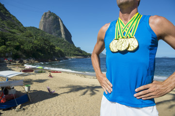 Gold medal athlete standing in front of Sugarloaf Mountain at Red Beach in Urca, Rio de Janeiro, Brazil