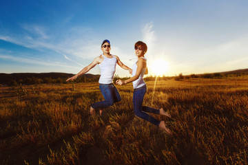 Young  happy couple is jumping for joy at golden summer field