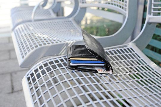 Verlorener Geldbeutel liegt auf einer Bank