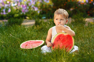 Caucasian little boy with blond hairs eating fresh watermelon in summer garden, outdoors.