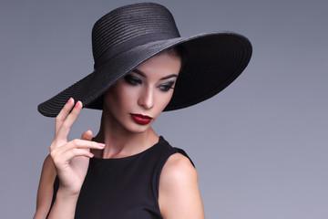 high fashion portrait of elegant woman in black hat.