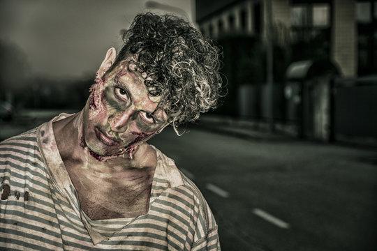 One male zombie standing in empty city street on Halloween