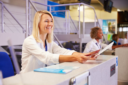 Staff Working At Airport Check In Desk