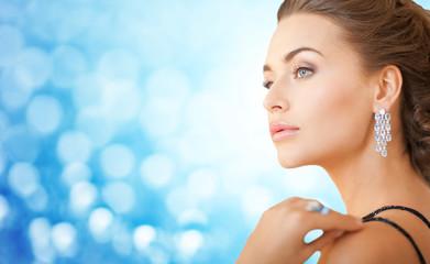 woman with beautiful diamond earrings over blue