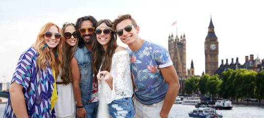 happy hippie friends with selfie stick at coliseum