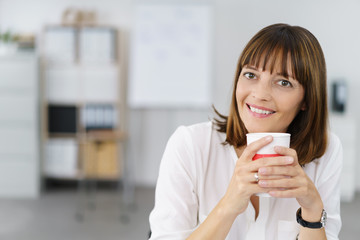 entspannte geschäftsfrau sitzt am schreibtisch mit einem becher kaffee