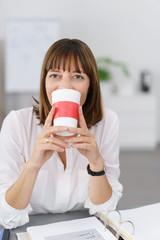 lachende frau mit einem becher kaffee am schreibtisch