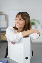 frau im büro stützt sich auf aktenordner und schaut zur seite