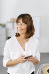 glückliche frau am arbeitsplatz hält ihr smartphone in der hand
