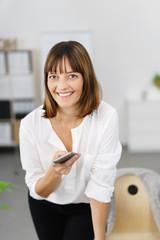 lächelnde frau im büro hält ihr mobiltelefon in der hand