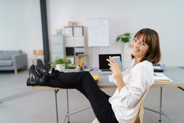 entspannte frau im büro legt die füße hoch und trinkt eine tasse kaffee